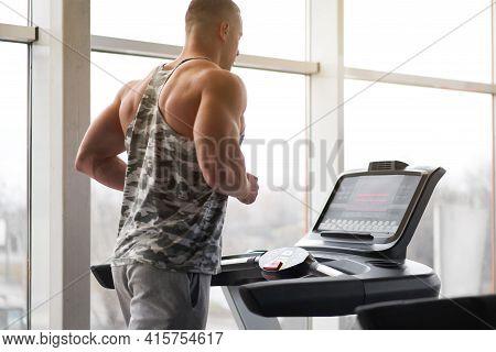 Muscular Athletic Bodybuilder Fitness Model Running Treadmill Gym Near Big Window Jogging Stationary