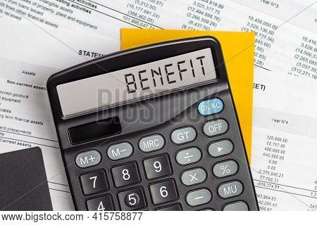 Benefit. On Display Of Calculator Is Written Benefit