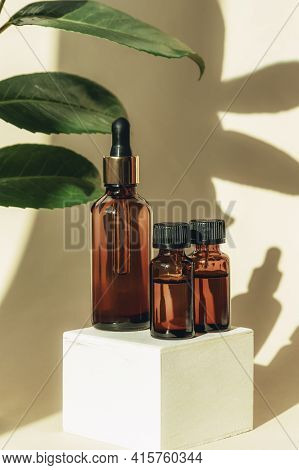 Natural Essential Oil Or Serum In Brown Glass Bottles On A Wooden Podium. Alternative Medicine, Beau