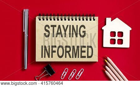 Staying Informed Text Written On Notebook With Pencils And Office Tools And Model Wooden House