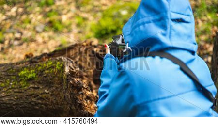 Girl With Blue Jacket Taking Pictures With Reflex Camera In Nature While Raining.