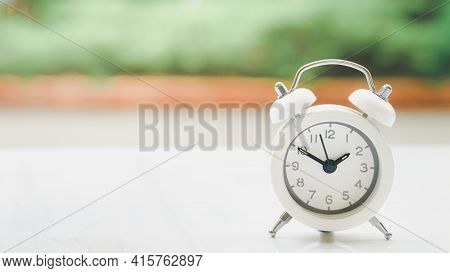 White Alarm Clock On Desk With Blurred Garden Background For Time Passing, Punctuality, Deadline, Bu
