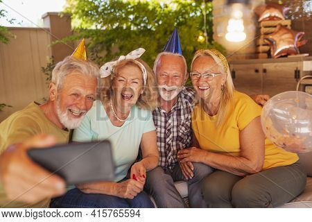 Group Of Cheerful Senior People Having Fun Celebrating Friend's Birthday, Wearing Party Hats And Tak
