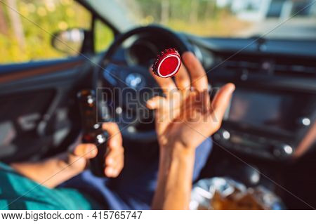 Young Man Drinking Beer In The Car And Throwing Out Bottle Cap. Focus On The Red Cap In The Air. Dri