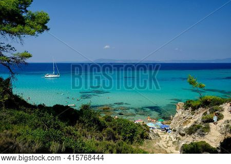 Chalkidiki, Greece - August 14, 2017 : A Sailboat And Tourists At The Beautiful Beach With Crystal C