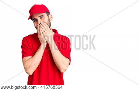 Young handsome man with beard wearing delivery uniform laughing and embarrassed giggle covering mouth with hands, gossip and scandal concept