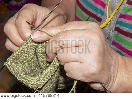 A Woman Knits Wool Socks With Knitting Needles.women\'s Hands Knit Knitting Needles Background.