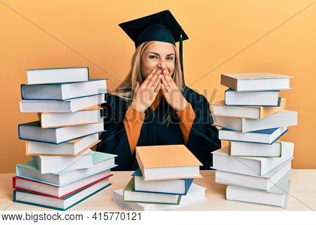 Young caucasian woman wearing graduation ceremony robe sitting on the table laughing and embarrassed giggle covering mouth with hands, gossip and scandal concept