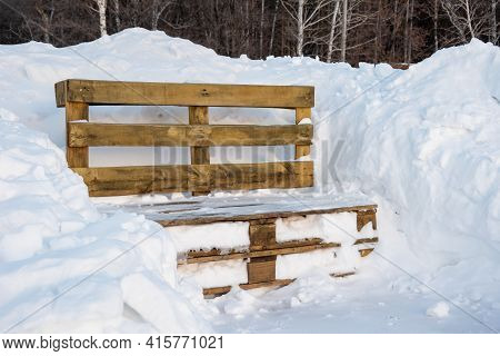 Wooden Bench From Pallets In A Snowdrift After A Snowfall In A Park In The Forest. Snowfall And Drif