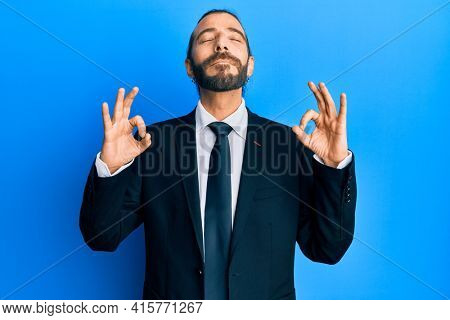 Attractive man with long hair and beard wearing business suit and tie relax and smiling with eyes closed doing meditation gesture with fingers. yoga concept.