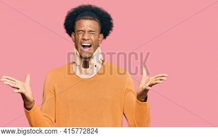 African american man with afro hair wearing cervical neck collar celebrating mad and crazy for success with arms raised and closed eyes screaming excited. winner concept