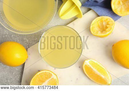 Freshly Squeezed Lemon Juice On Grey Table, Flat Lay