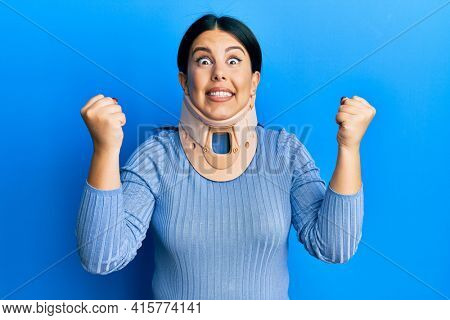 Beautiful brunette woman wearing cervical collar screaming proud, celebrating victory and success very excited with raised arms