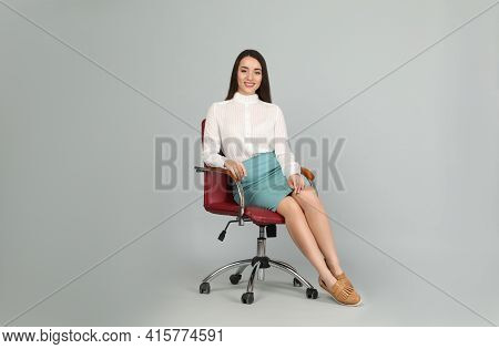 Young Businesswoman Sitting In Comfortable Office Chair On Grey Background