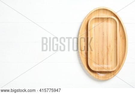 Empty Clean Wooden Dishware On White Table, Top View. Space For Text