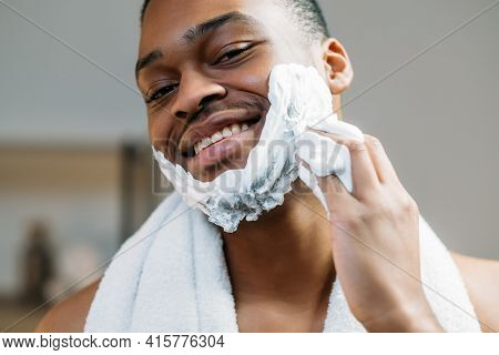 Man Grooming. Facial Treatment. Selfcare Routine. Cheerful Relaxed African Guy With White Towel Enjo