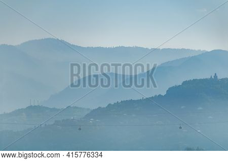Multilayered Foggy Mountains. Mountain Peaks In Morning Haze.  Landscape Layers Of Hills In The Haze