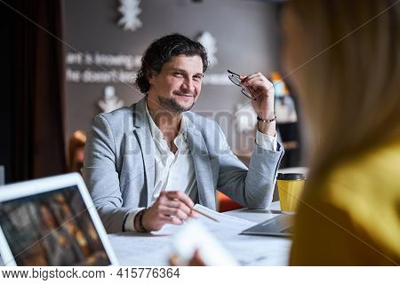 Positive Delighted Brunette Man Looking At His Colleague