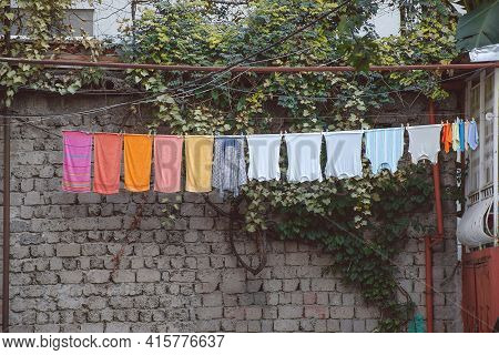 Washed Clothes Hang In A Line And Dry In The Backyard At The Brick Wall Background. Batumi, Georgia
