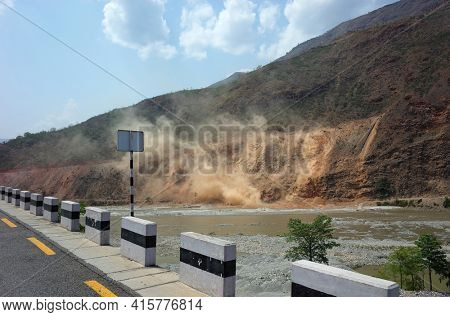 Himalayas, Nepal - June 12, 2019: Dangerouse construction of new road in mountain, Wind blowing large dust clouds from landslides