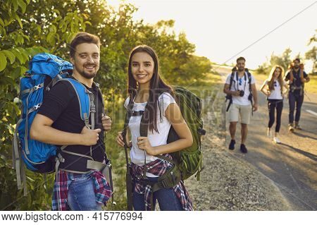 Hiker Couple With Backpacks In Nature. A Group Of Friends Are Hiking The Route Along The Road In The