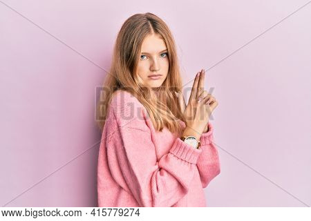 Beautiful young caucasian girl wearing casual clothes holding symbolic gun with hand gesture, playing killing shooting weapons, angry face