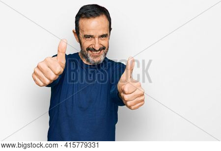 Middle age hispanic man wearing casual clothes approving doing positive gesture with hand, thumbs up smiling and happy for success. winner gesture.