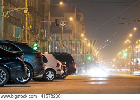 Close Up Of Parked Cars On Roadside At Night With Blurred View Of Traffic Lights Of Moving Vehicles
