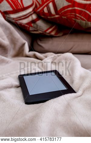 An E-reader On A Blanket On A Sofa. Concept Of Peace Of Mind At Home, Reading At Home, Hobbie At Hom