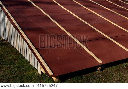 Roof Tiles Made Of Plastic Asphalt Foil. View Of Rows Of Red Brown Narrow Recycled Strips, Asphalt,