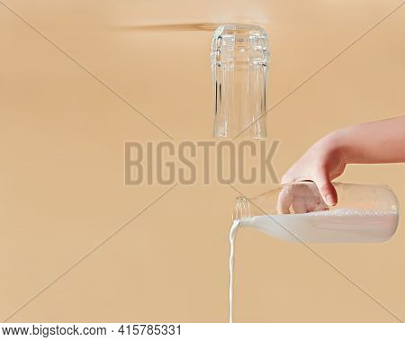 Milk Pouring Out Of A Glass Bottle. Glass Turned Upside Down. Creative Dairy Product Concept. Copy S