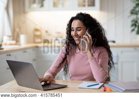 Telecommuting. Smiling Lady Talking On Cellphone And Working With Laptop In Kitchen