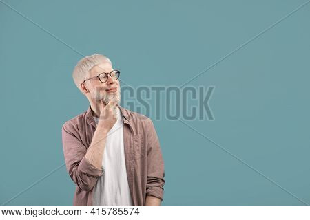 Pensive Albino Guy Thinking Over Decision, Looking At Empty Space Over Turquoise Studio Background