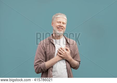 Sincere Albino Guy Holding Hands On Chest, Expressing Gratitude And Positive Emotions On Turquoise S
