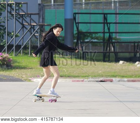 Asian Women Play Surf Skates Board Outdoors On Beautiful Summer Day. Happy Young Women Play Surfskat