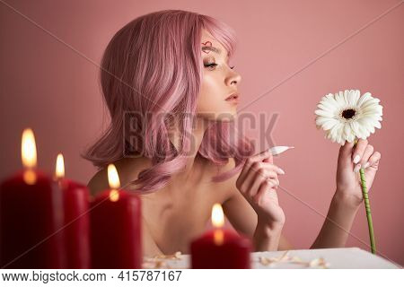 Beautiful Woman With Dyed Pink Hair Guessing At Flower In Hand At Table With Candles. Pink Beauty Ha