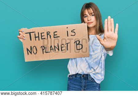Teenager caucasian girl holding there is no planet b banner with open hand doing stop sign with serious and confident expression, defense gesture
