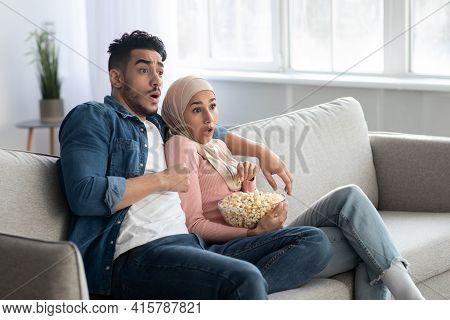 Shocked Muslim Couple Watching Thriller, Home Interior