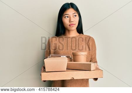 Young chinese woman holding take away food smiling looking to the side and staring away thinking.