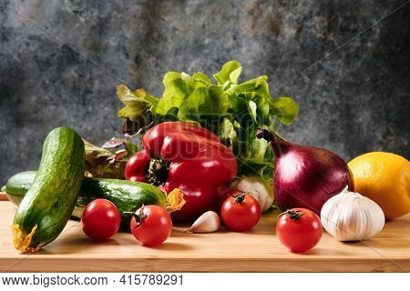 Cucumber, tomatoes, peppers, garlic and lettuce on a dark background