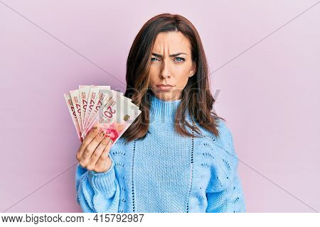 Young brunette woman holding 20 israel shekels banknotes skeptic and nervous, frowning upset because of problem. negative person.