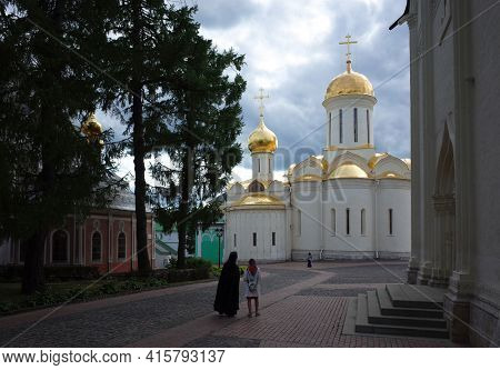 Sergiyev Posad, Russia - June 25, 2019: Trinity cathedral in the Trinity Lavra of St. Sergius, Holy Father in black clothes and woman walk to old Russian church under grey sky