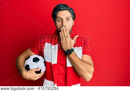 Young hispanic man football hooligan holding ball covering mouth with hand, shocked and afraid for mistake. surprised expression