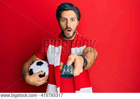 Young hispanic man football hooligan holding ball using tv control afraid and shocked with surprise and amazed expression, fear and excited face.