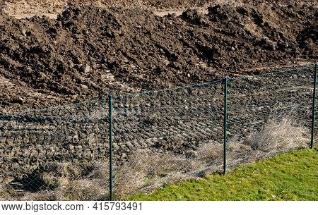 Bulldozer Performs Topsoil Raking. The Land Behind The Wire Fence Is Now A Construction Site De The