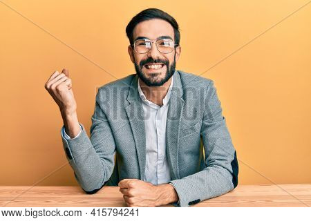 Young hispanic man working at the office screaming proud, celebrating victory and success very excited with raised arm