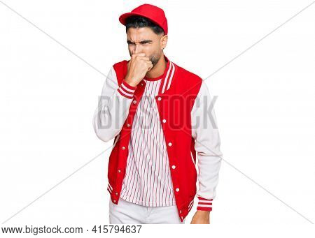 Young man with beard wearing baseball uniform smelling something stinky and disgusting, intolerable smell, holding breath with fingers on nose. bad smell