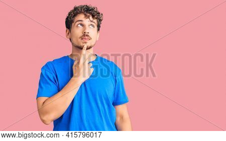Young handsome man with curly hair wearing casual clothes thinking concentrated about doubt with finger on chin and looking up wondering