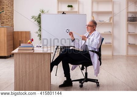 Old male doctor cardiologist sitting in the classroom