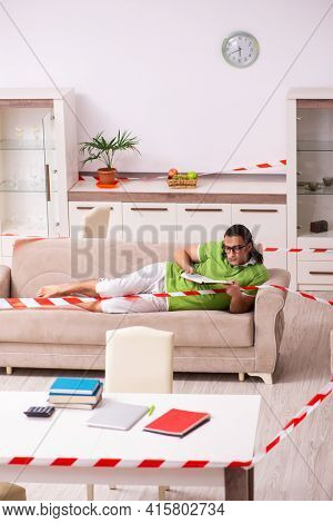 Young male student studying at home in self-isolation concept
